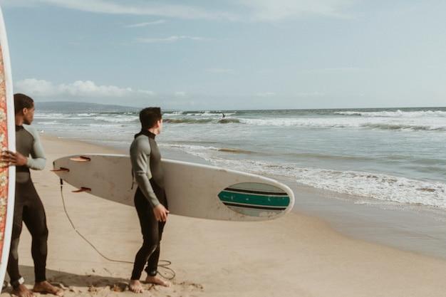 Мужчины смотрят на серфера на пляже