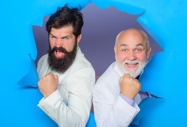 Men making hole in paper emotions successful men look through hole in paper bearded men peeking from