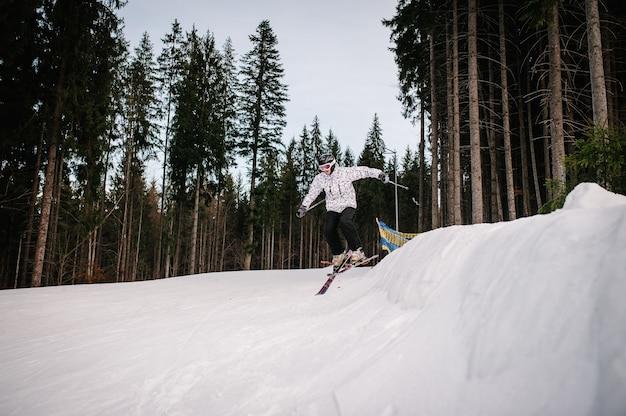 スキーをしている男性は、カルパティア山脈の雪の上で飛び込み台のスキージャンプから丘からジャンプします。背景の森とスキー場。閉じる。