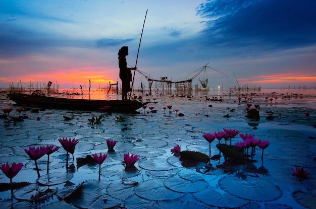 보트에 탄 남자들이 태국 남부 파탈룽 지방의 관광명소로 호수에서 작은 낚시를 하고 있다