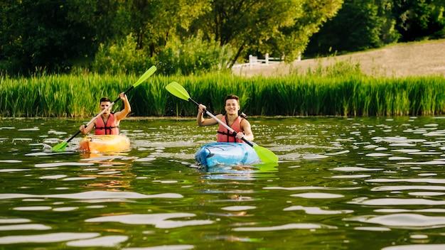 Men paddling kayak on ripple water