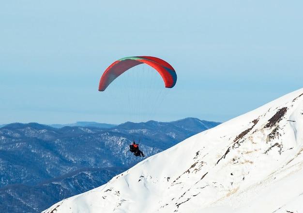 冬の雪山でパラグライダーをする男性。エクストリームスポーツ