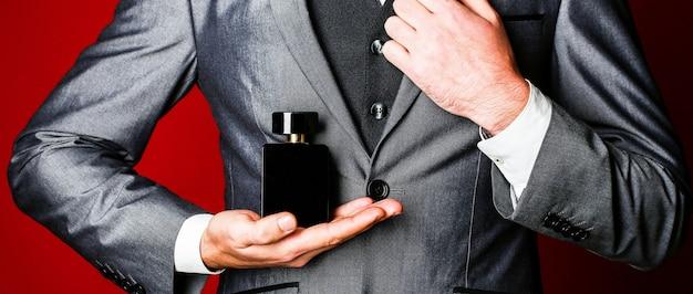 남자 정장 배경에 손에 향수. 향기 냄새. 남성 향수. 패션 향수 병. 공식적인 양복, 향수 병, 근접 촬영에 남자.