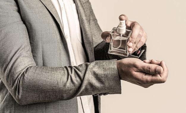 양복 배경에 손에 남자 향수입니다. 정장을 입은 남자, 향수 한 병, 근접 촬영. 향수 냄새. 남자 향수. 패션 향수 병.