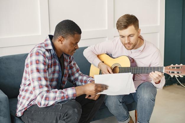 男性はギターを弾きます。音楽を書く。アフリカ人と白人男性。
