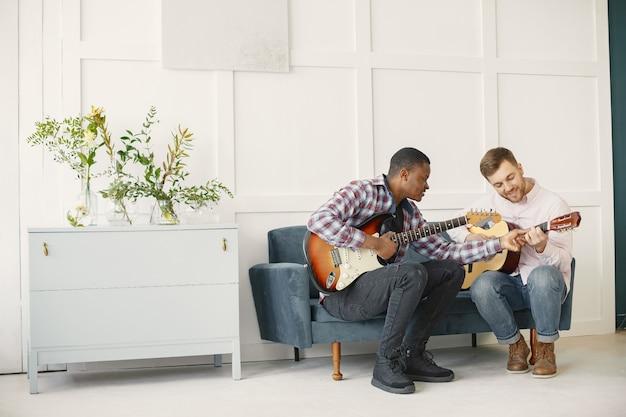 Men play guitar. writing music. african and caucasian men.