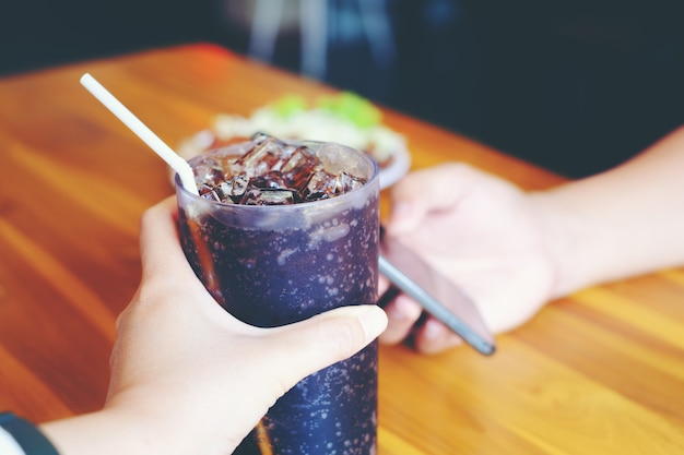 Men play smartphone and woman hand giving glass of cola. glass of cola
