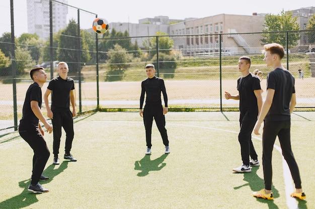 Мужчины играют в клубок в парке. турнир по мини-футболу. парень в черном спортивном костюме.