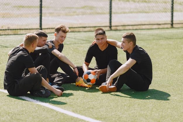 男性は公園でソーサーをします。ミニサッカーのトーナメント。黒のスポーツスーツを着た男。