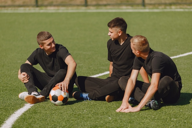 Men play socer at the park. tournament on mini-footbal. guy in a black sportsuits.