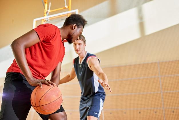 Men playing basketball together