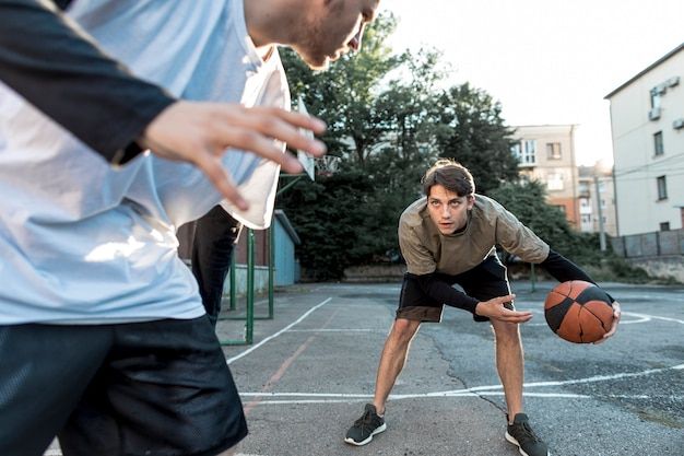 Men playing basketball on urban court
