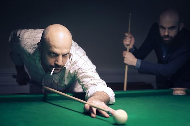 Men playing billiard in a bar