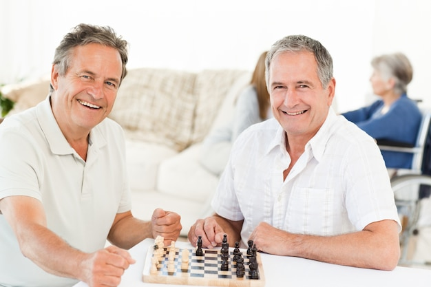 彼らのwifesが話している間チェスをしている男性