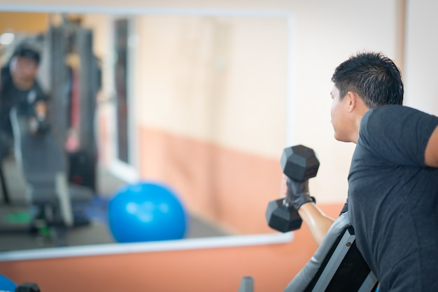 Men playing dumbbell rise beside body and on floor in gym exercise