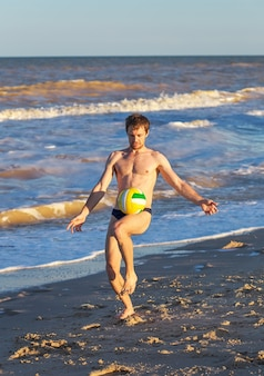 Men playing football on the beach coast at sunset