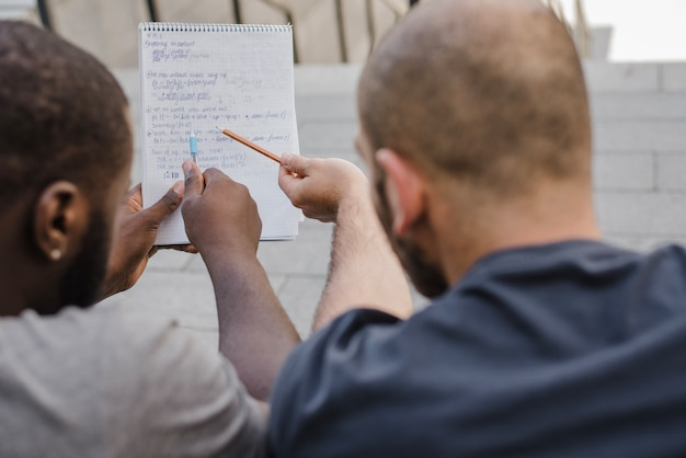 Men pointing at notebook outside