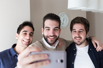 Men posing for selfie in office