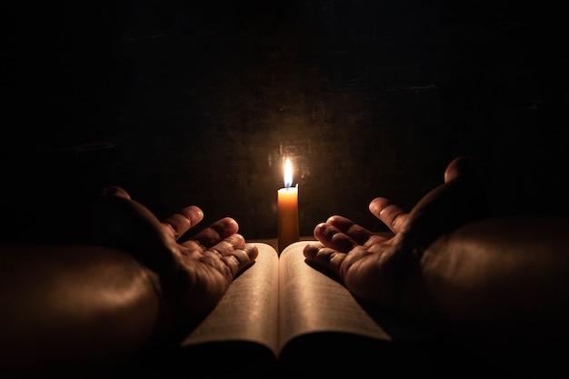 Men praying on the bible in the light candles selective focus.