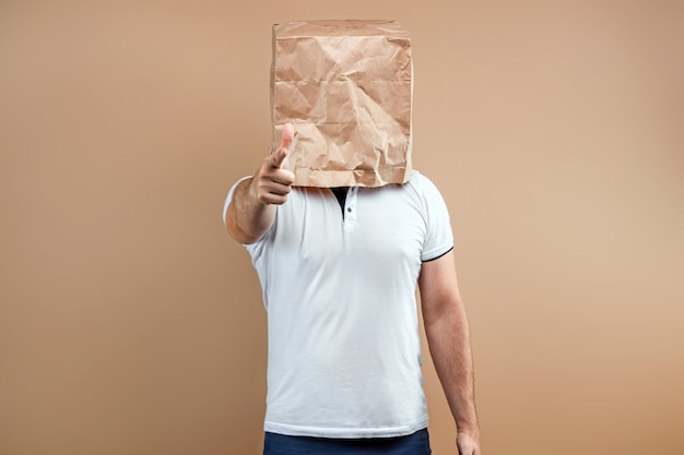 Men put a paper bag on their heads, point a finger at you. isolate on yellow background, images are easy to crop for use anywhere, copy space.