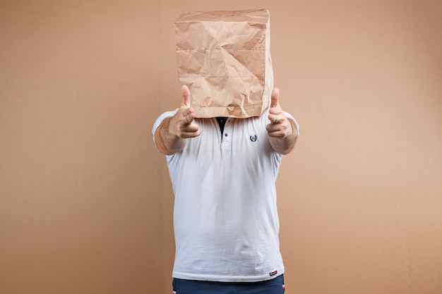 Men put a paper bag over their heads, shoots their fingers at you isolate on yellow background, images are easy to crop for use anywhere, copy space.