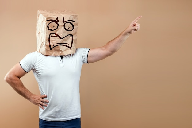 Men put a paper bag on their heads with a drawn screaming face, points a finger at you isolate on a yellow background, images are easy to crop for use anywhere, copy space.