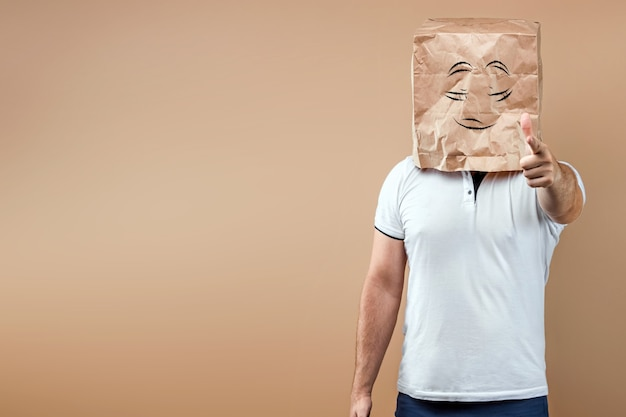 Men put a paper bag over their heads with painted eyes on it, points a finger at you. isolate on yellow background, images are easy to crop for use anywhere, copy space.