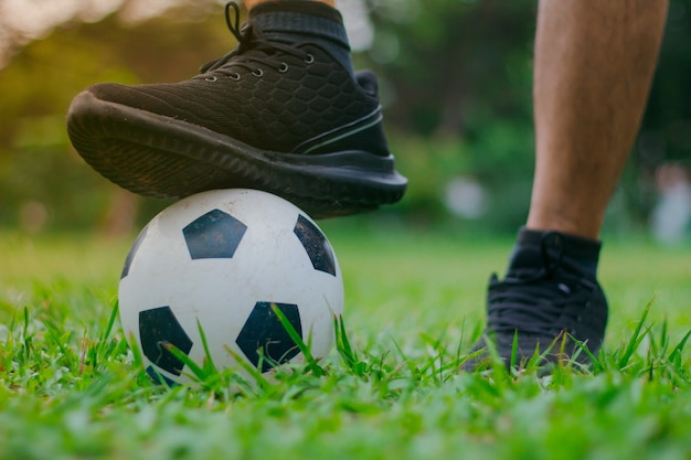 Men put their feet on the soccer ball.