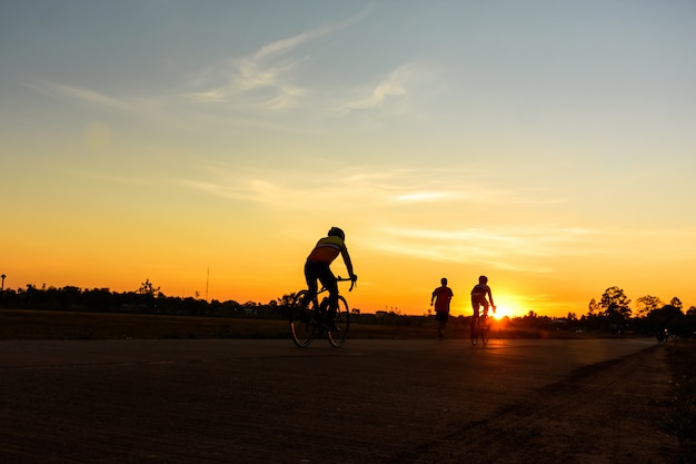 男性は美しい色鮮やかな夕焼け空の道で自転車に乗る。スポーツと活動的な生活の概念。