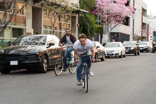 Uomini che guidano le biciclette nel colpo pieno della città