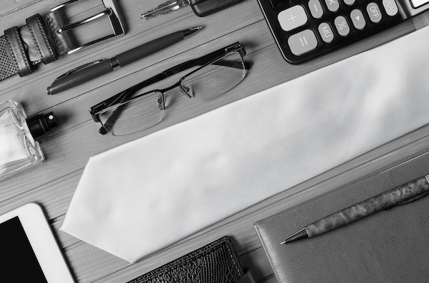 木製のテーブルにメンズアクセサリーとネクタイ。現代の成功した人のイメージの概念。