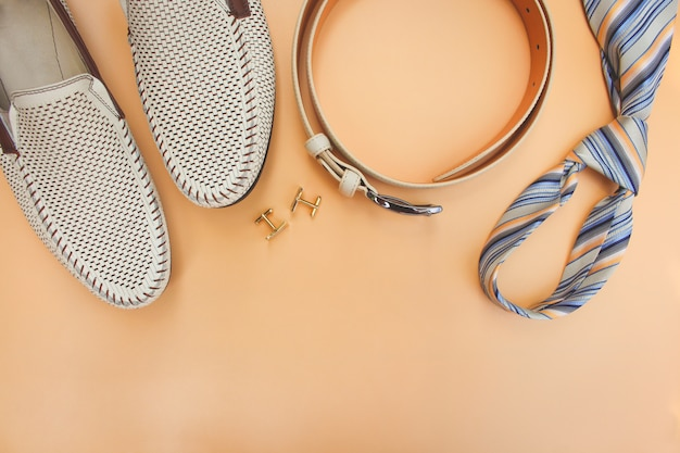 Men's accessories on beige background. top view.