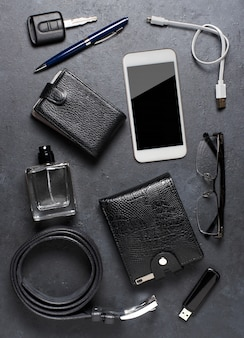 Men's accessories on a black concrete background. concept of a successful modern man