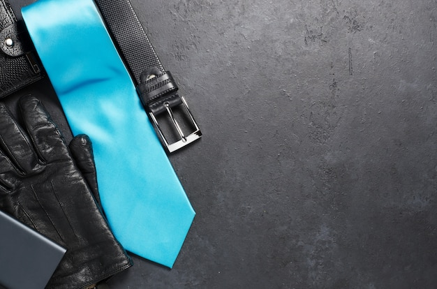 Men's accessories and clothing on a black concrete