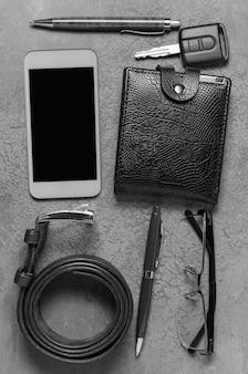 Men's accessories on a dark concrete surface