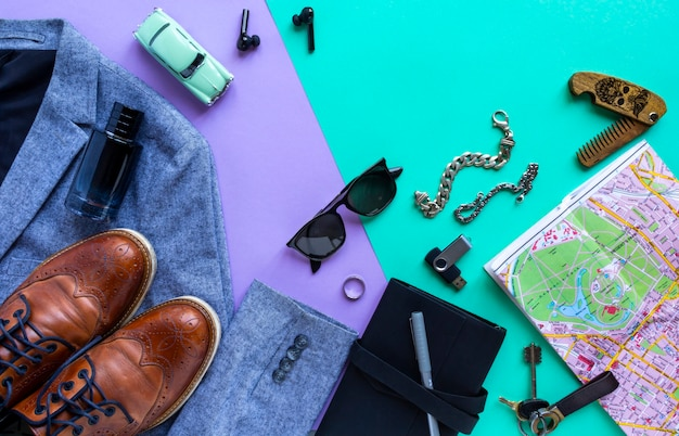 Men's accessories, devices on lilac and turquoise background. concept of cancellation travel and vacation, top view, flat lay.