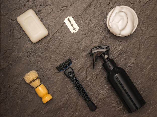 石の背景に剃ったり洗ったりするためのメンズアクセサリー。男の顔のケアのために設定します。フラットレイ。