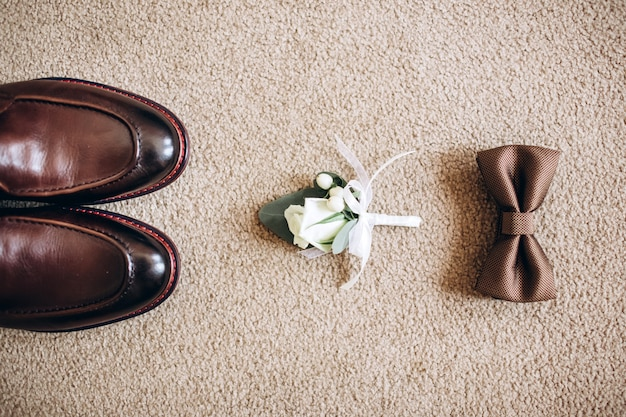 Мужские аксессуары, кожаный ремень, духи, галстук-бабочка, золотые кольца жениха, часы и невесты на белом столе. концепция детали одежды бизнесмена