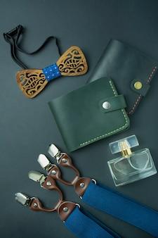 メンズアクセサリー。暗い背景に男性用財布、男性用蝶、サスペンダー、香水。メンズキット。テキストのためのスペース。コピースペース。