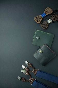Men's accessories. men's wallet, men's butterfly, suspenders and perfume on a dark background