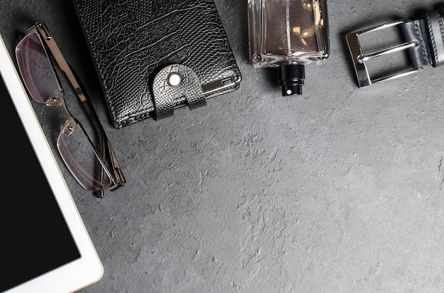 Men's accessories and tablet on a black concrete
