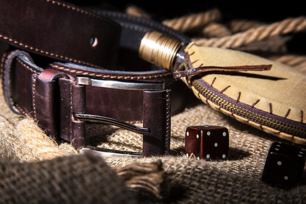 Men's accessories with brown leather belt, sunglasses, watch, smoking pipe and bottle with perfume