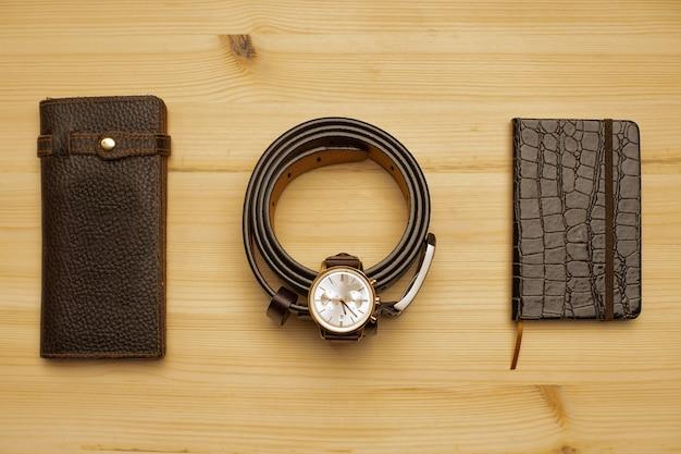 나무 표면에 갈색 가죽 지갑, 벨트, 노트북 및 시계가있는 남성용 액세서리