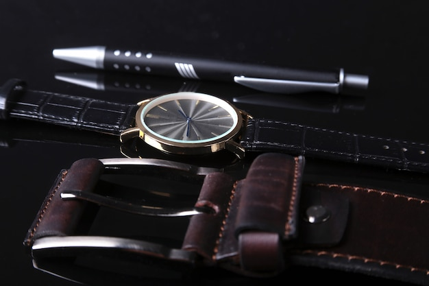 Men's accessories with brown leather wallet, belt and watch.