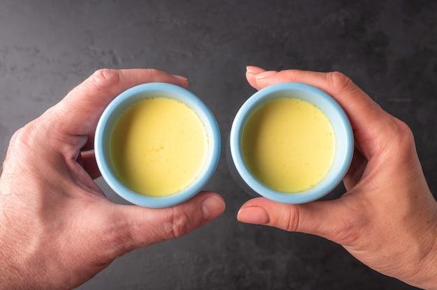 男性と女性の手は伝統的なインドのマサラチャイ茶と並んで青いセラミックカップを保持します。