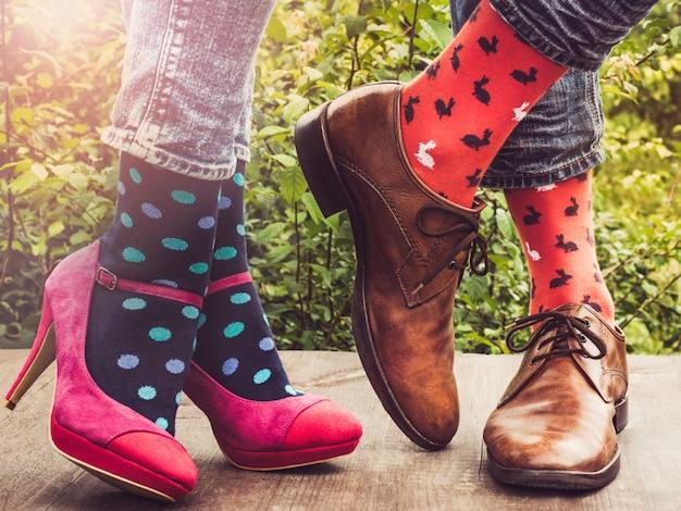 男性と女性の足、明るい靴下。