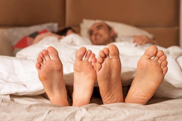 Мужские и женские ножки торчат из-под одеяла.