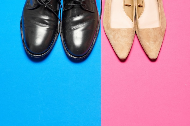 Мужская и женская обувь на синем и розовом красочном фоне. деловая рабочая обувь с копией пространства плоской планировки. вид сверху