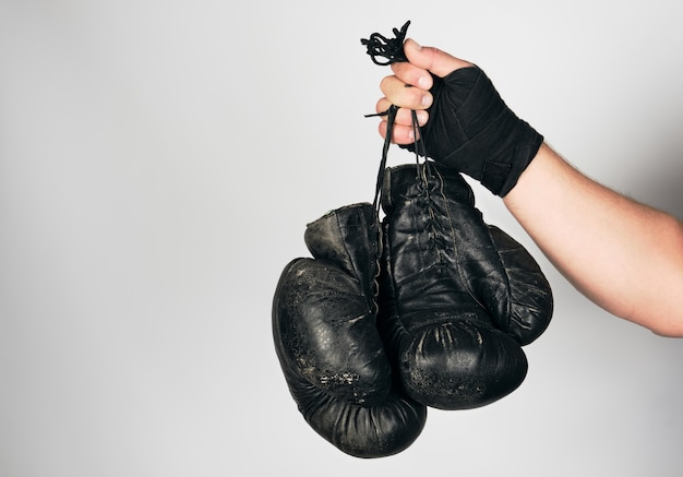 Men's arm wrapped in a black elastic sports bandage holds old vintage leather boxing gloves