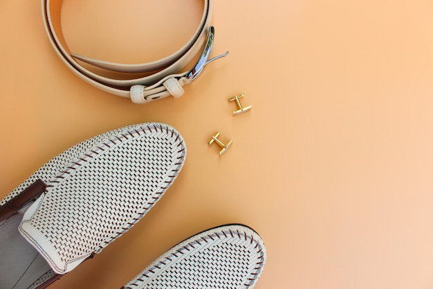 Men's belt, shoes, cufflinks on beige background.